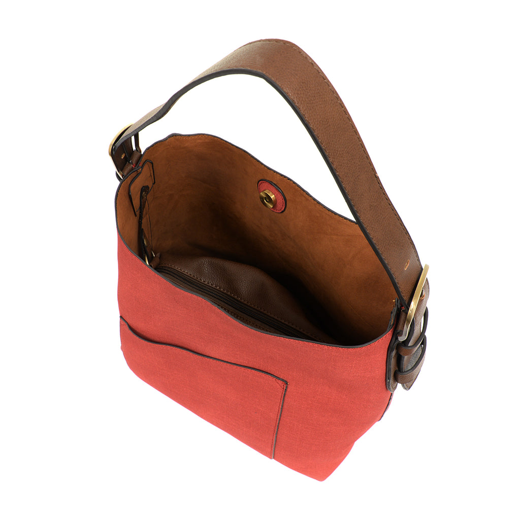 View of the inside of red faux linen hobo bag with brown buckle strap, and accompanying brown insert bag with cross body strap.