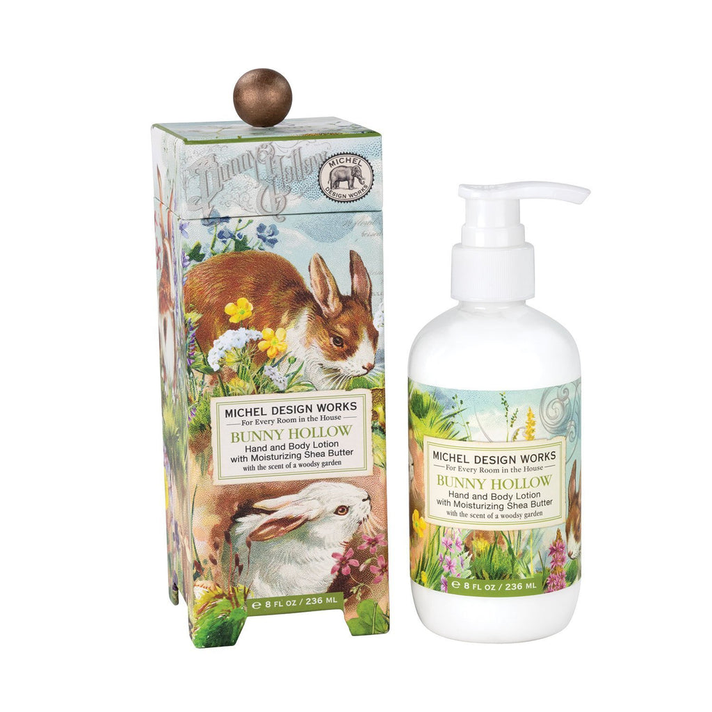 A decorative box with an image of bunnies frolicking in a hollow surrounded by spring flowers next to a bottle of hand and body lotion with a corresponding label.