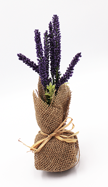 Posable lavender stems and mixed greens are fixed in a foam base wrapped in burlap and finished with a jute bow.