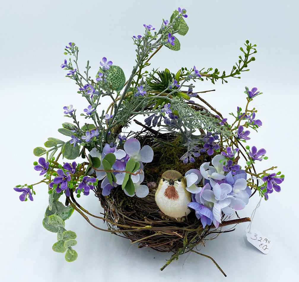 A floral arrangement with a bird nest in the middle and is surrounded by violets, purple hydrangeas and eucalyptus.