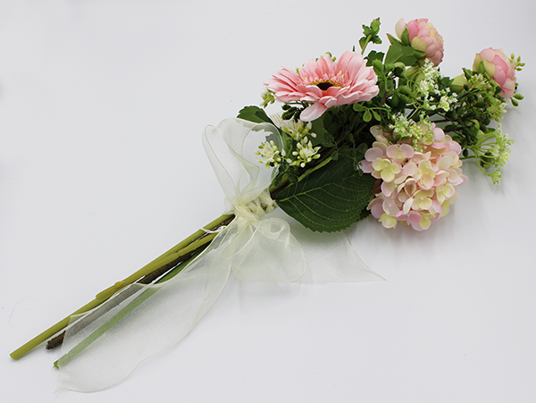 An artificial arrangement on a white background that features pink hydrangeas, gerber daisies, Queen Anne's lace, and ranunculus.