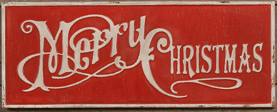 Red metal sign with the text 'Merry Christmas' in a vintage script, surrounded by a cream colored frame.  Sign is on a wooden background.