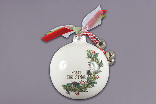 White ornament with illustrated garland in greens and red curling up from the bottom to the top, around hand written text 'Merry Christmas'.  The top of the ornament has red, green, and white ribbon tied around the hook, as well as three jingle bells.