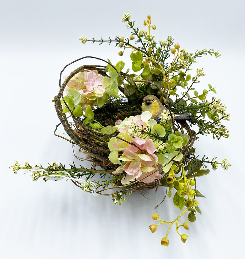 A birds nest floral arrangement surrounded by twigs and flowers.  Most of the flowers are on the right side and are in an asymmetrical grouping curving around to the left.  Flowers on the outside of the nest are pink hydrangeas, eucalyptus and astilbe.
