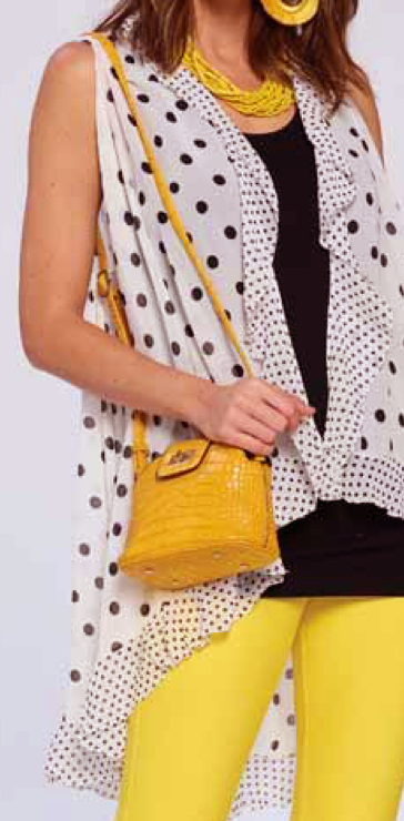 A model wearing a black top with a white and black polka dot ruffled top over it.  She is also wearing yellow pants and coordinating earrings and beaded necklace.  She is holding a purse that has a strap over her shoulder.  The purse and strap is yellow with an alligator embossed texture.