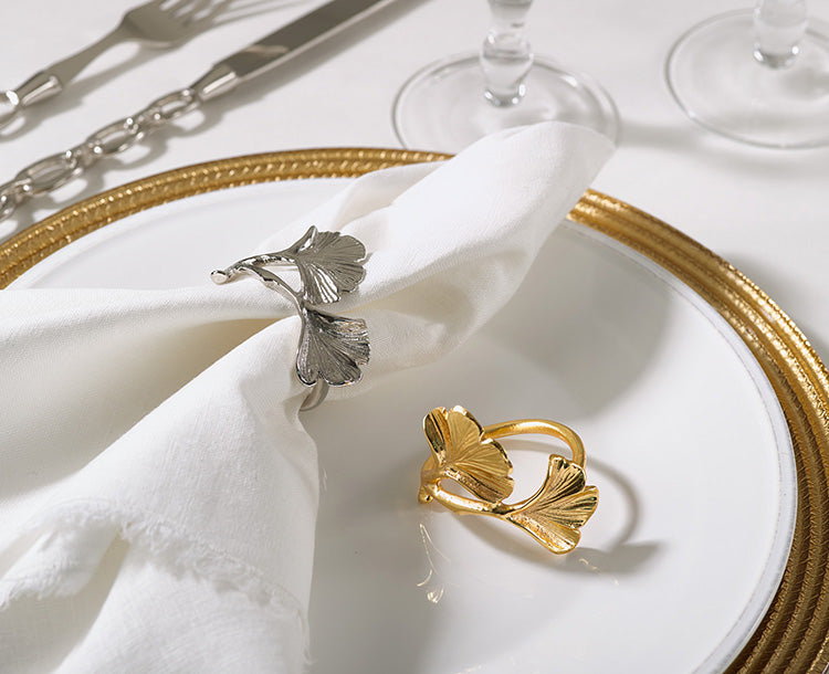 A place setting on a white table cloth.  On top of a gold charger is a white plate.  On the white plate is a napkin with a silver napkin ring with two leaves on it inspired by the ginko leaf.  Next to the napkin is the same napkin ring in gold.