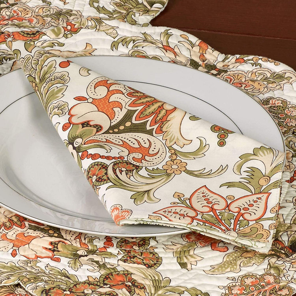 Jacobean flourish design printed on a cotton napkin in tan, green and orange.  Napkin is folded and placed on a white plate.  Plate is placed on a coordinating placemat with scalloped edges.