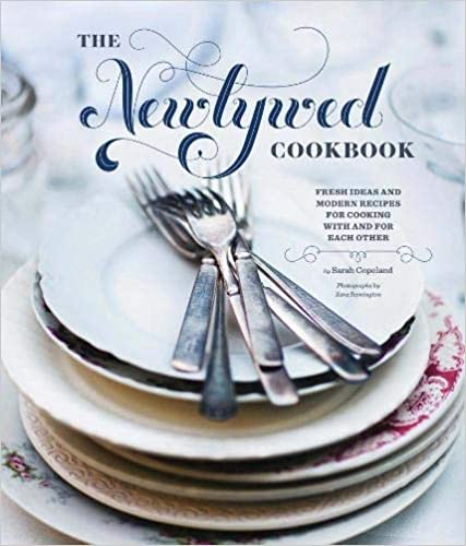"The book cover of ""The Newlywed Cookbook"" - shows a stack of plates with cutlery on top.  Text to the side of the plates says 'Fresh ideas & modern recipes for cooking with and for each other'"