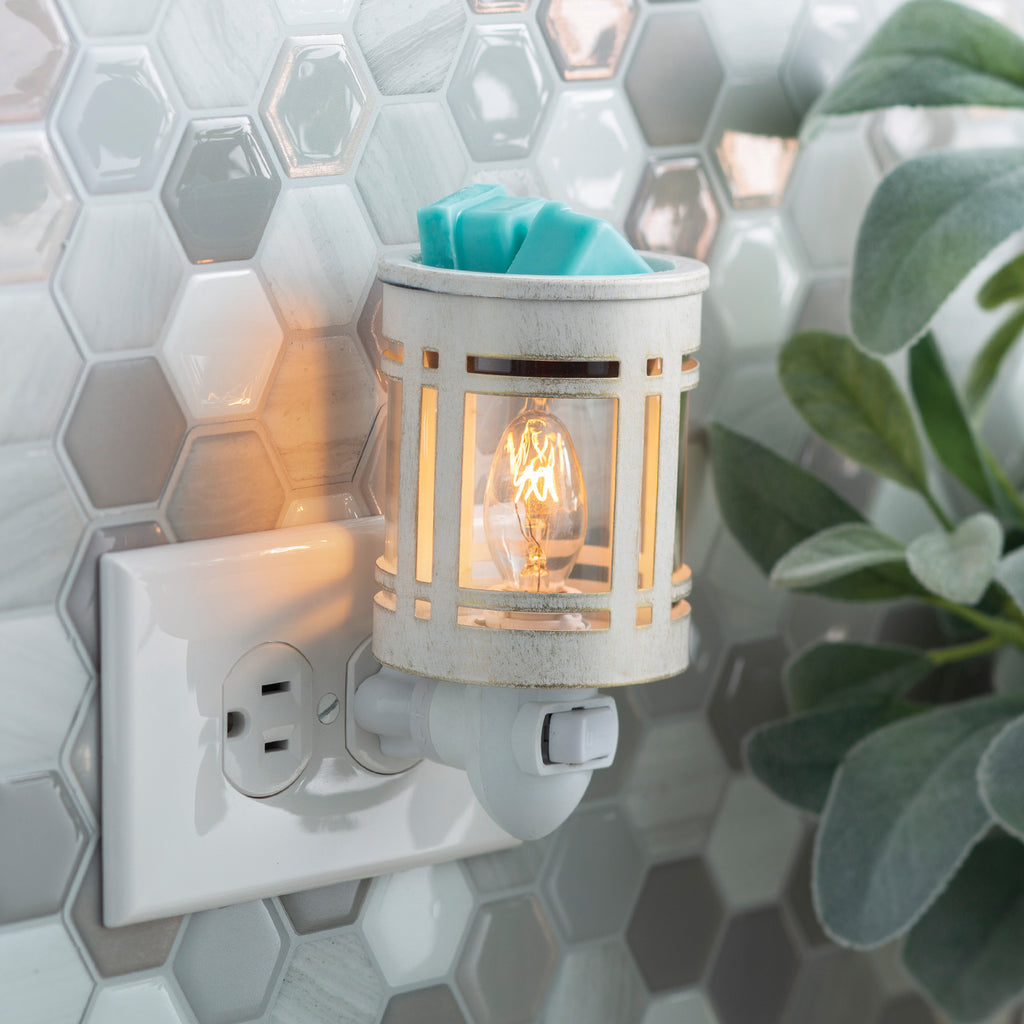 White metal wax melt warmer in the style of a mission light fixture, with clear glass showcasing the light bulb inside.  The outlet is on a wall tiled with hexagonal gray and white tiles.