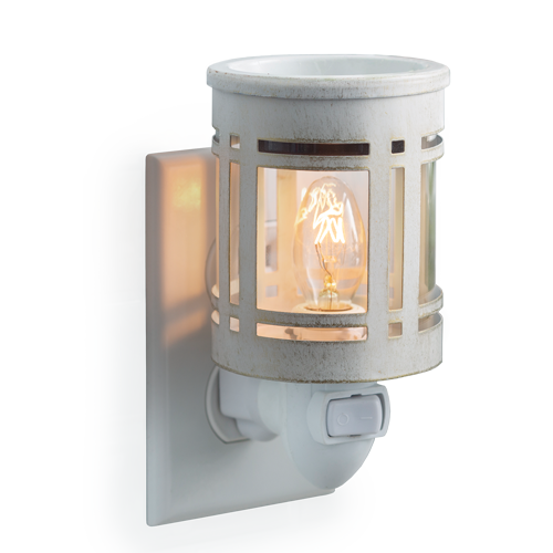White metal wax melt warmer in the style of a mission light fixture, with clear glass showcasing the light bulb inside.