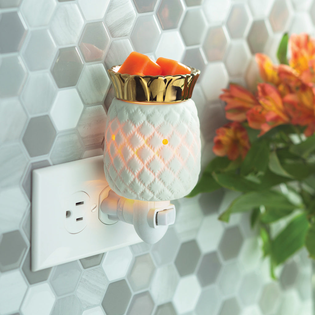 Pineapple wax warmer plugged into an outlet on a wall with hexagon shaped tile.  White ceramic pineapple has a warm internal glow and has gold metallic fronds where the wax sits.