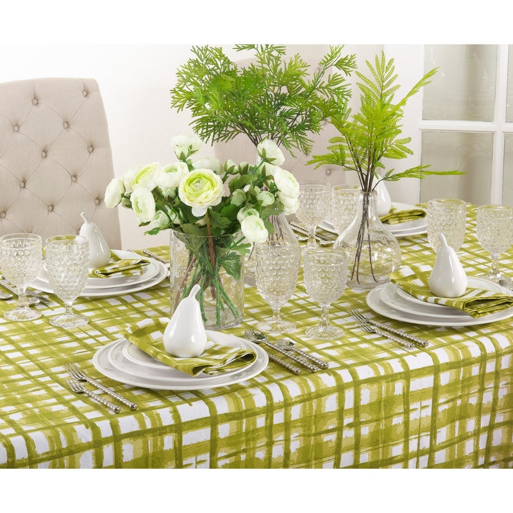 A set table on a white table cloth with green plaid pattern that is reminiscent of a watercolor painting.  Alternating wide and narrow strokes add whimsy to your tablescape.