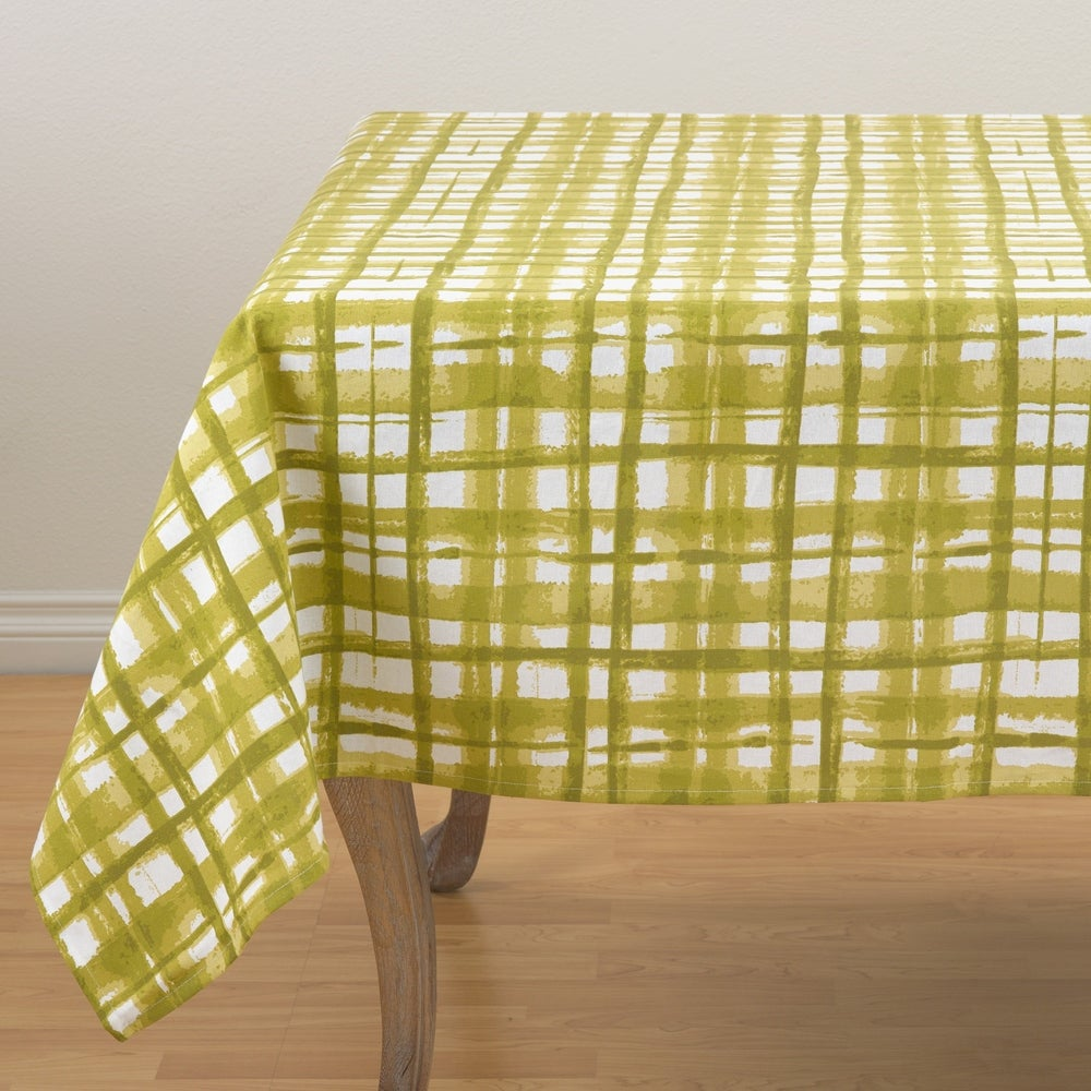 A white table cloth with green plaid pattern that is reminiscent of a watercolor painting.  Alternating wide and narrow strokes add whimsy to your tablescape.