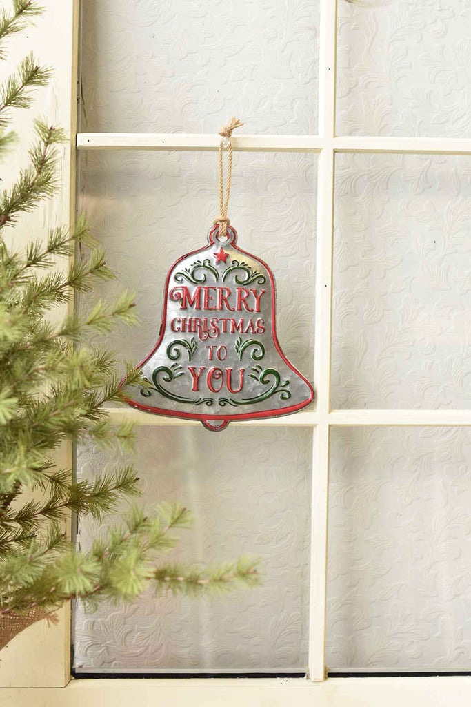 "Galvanized bell with filigree and text that says ""Merry Christmas To You"".  Text is in red, filigree is in green.  Bell is outlines in red.  In photo, the bell is hung on a window mullion next to an evergreen tree."