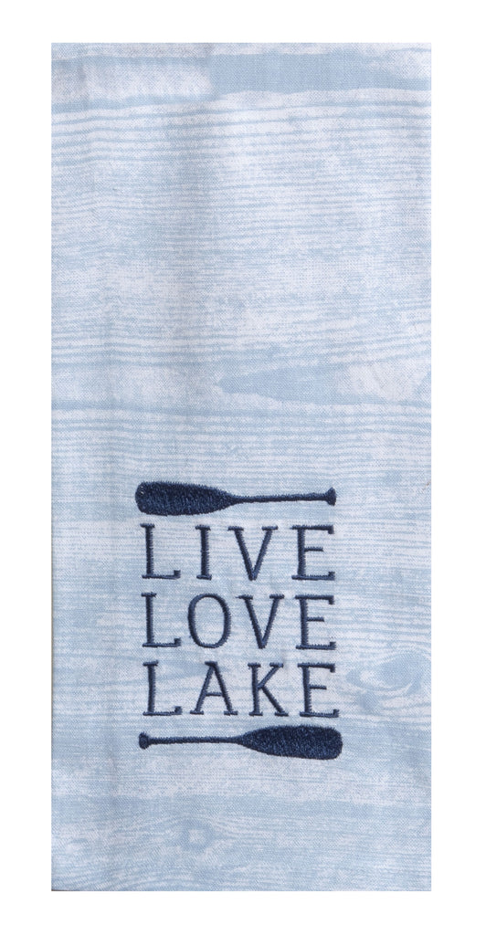 The front of a kitchen towel that has a printed pattern of wood grain in a blue hue, which looks similar to ripples in water.  Towards the bottom are navy embroidered horizontal canoe paddles with text in-between that says 'live love lake', each on separate lines.