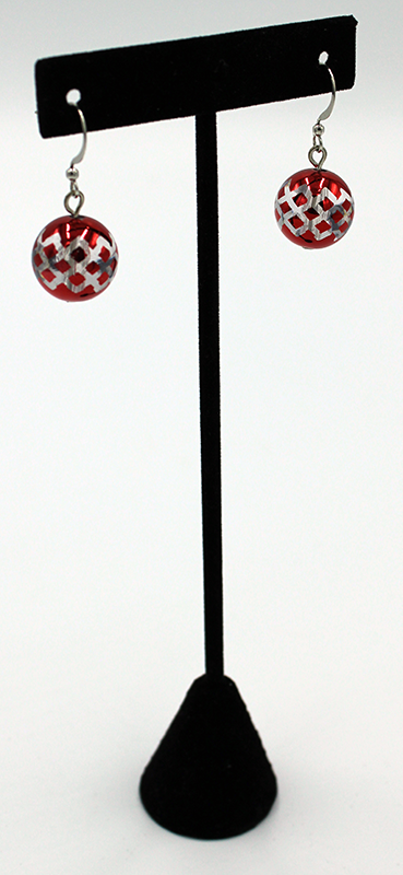 Red metallic ornament earrings on a display stand.