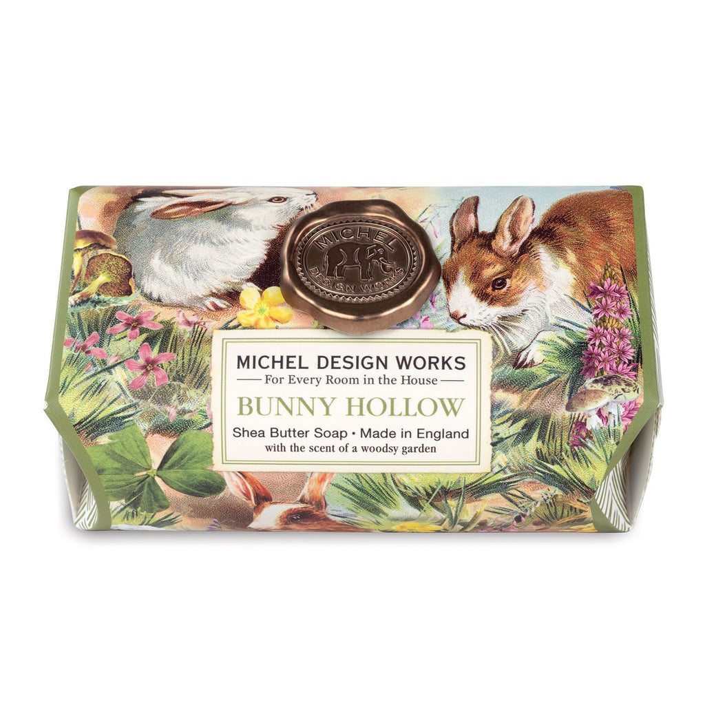 A bar of soap wrapped in a decorative printed package with a metallic bronze wax seal.  The image is of bunnies frolicking in a hollow surrounded by spring flowers.