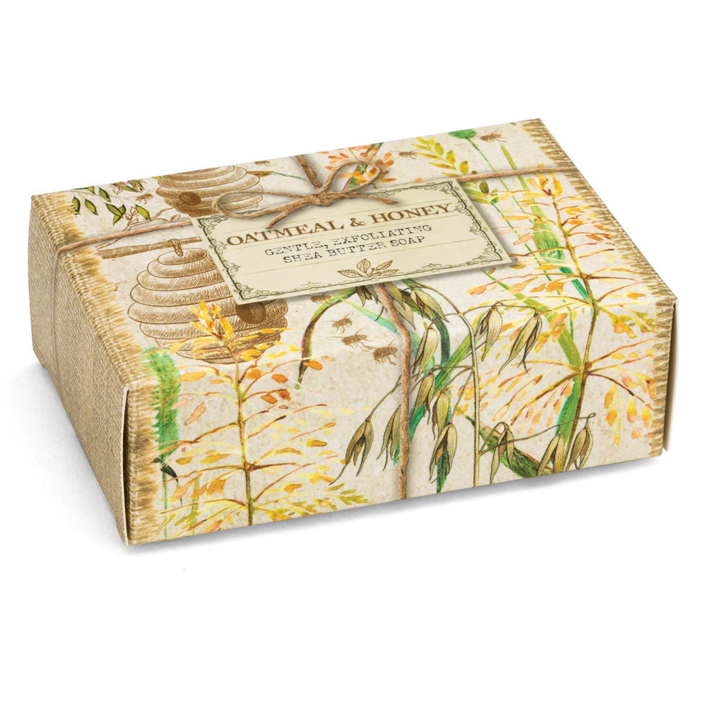 Oatmeal & Honey bar of soap in a cardboard gift box.  Box is printed with an artistic scene of bee hives, wheat, trees, and twine.  The label reads 'Oatmeal & Honey Gentle Exfoliating Shea Butter Soap""