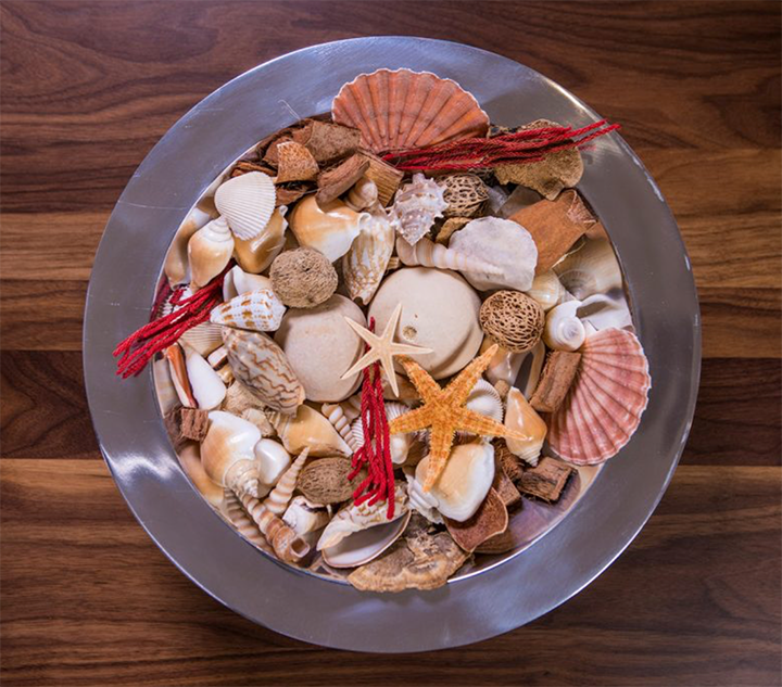 Bowl of potpourri on a wooden table, from above.  Contents of bowl include various shells, starfish, and dried scented items.