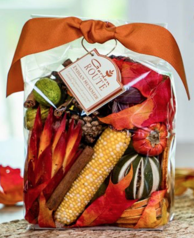 A clear bag of potpourri with leaves, flowers, cinnamon, and other fall festive dried elements.