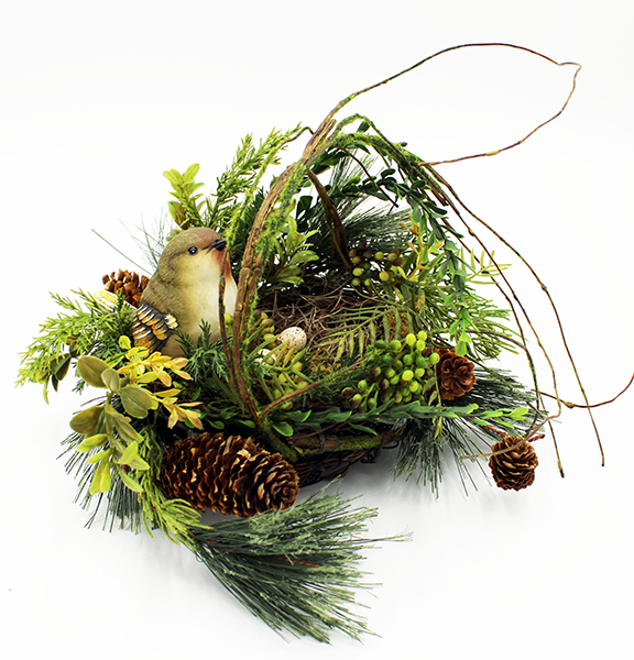 Round floral arrangement of birds nest with an artificial bird, pinecones, ferns, and mixed woodland greens