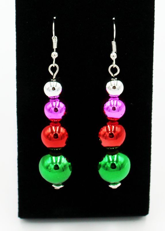 Stacked ornament earrings.  Each earring has a large green sphere at the bottom, with a red one on top, a pink on on that, and finally a silver one on top.