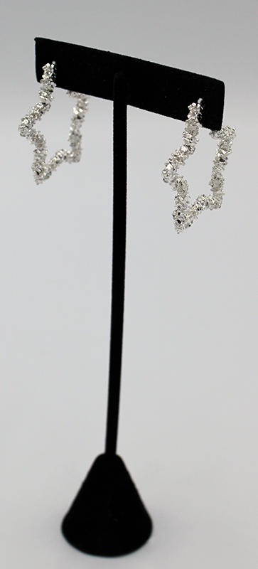 Shimmering star earrings with open middle on a black display rack.