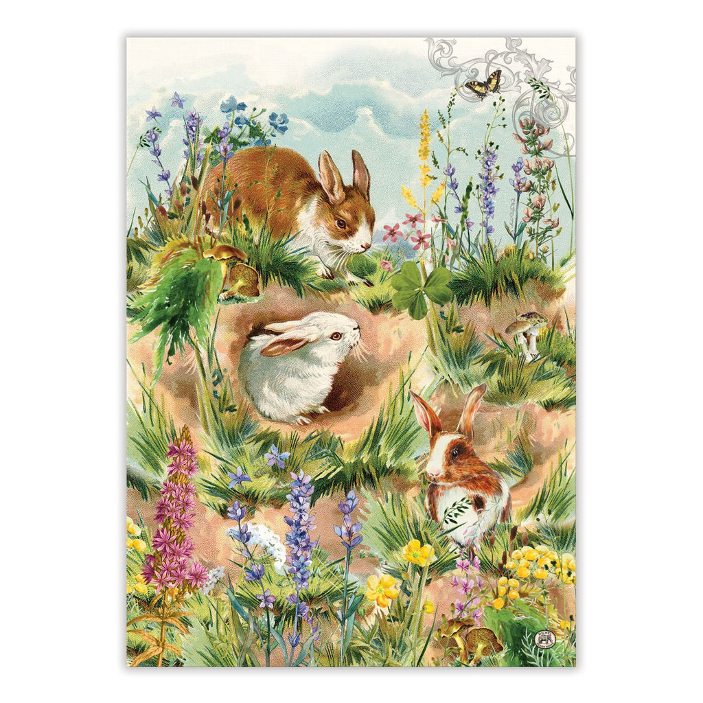 Kitchen towel with printed artwork of brown and white bunnies frolicking around a hollow.  They are surrounded by colorful spring flowers and butterflies.
