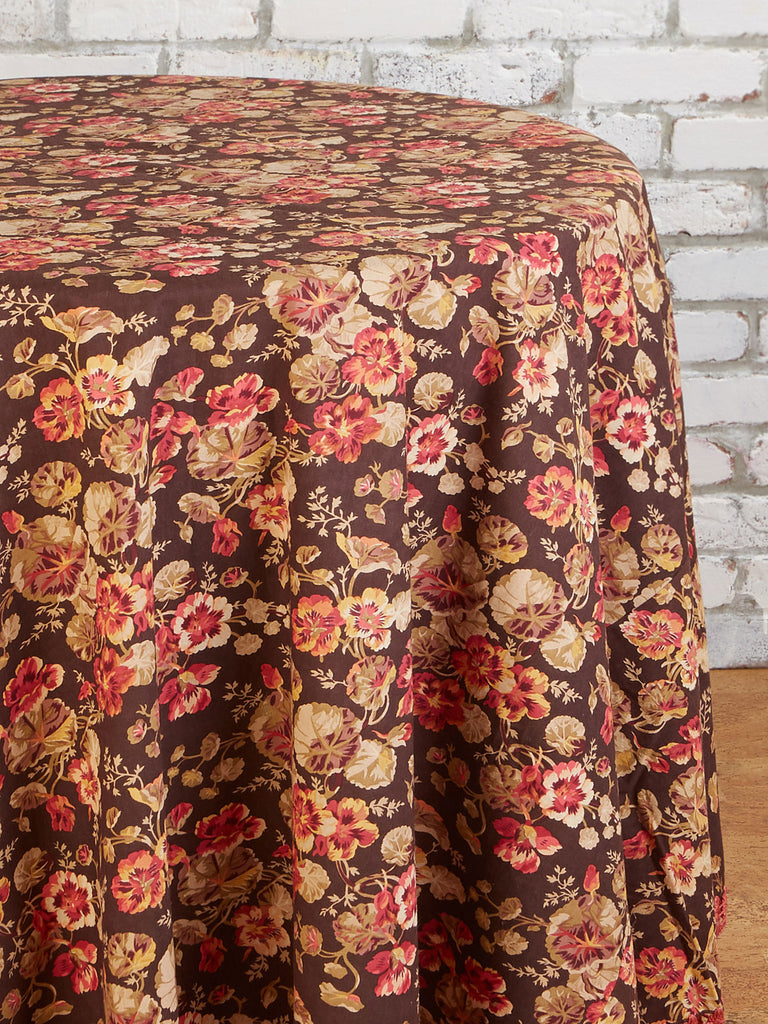 Close up of a floral tablecloth on a round table in front of a white brick wall.  Table cloth has a dark brown background, tan and red flowers, and a woven dark pink bottom detail.
