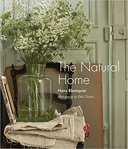 "Cover of ""The Natural Home"" features a large vase of Baby's Breath in water on a chair with folded muslin sitting in front of a rustic light green door."
