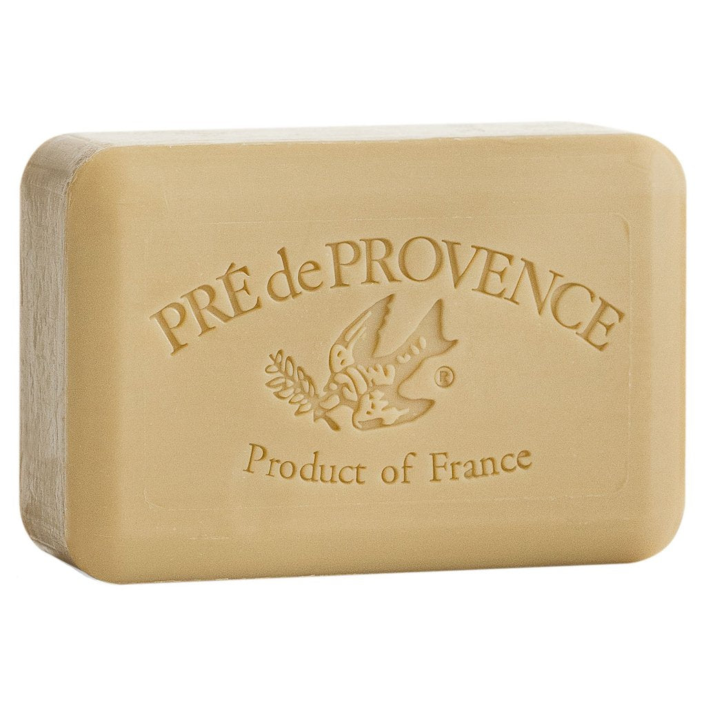 A tan bar of soap on white background.  A bird with a stem of greenery in its mouth is embossed in the center.  Text above the bird says 'Pre de Provence'.  Text below the bird says, 'Product of France'.