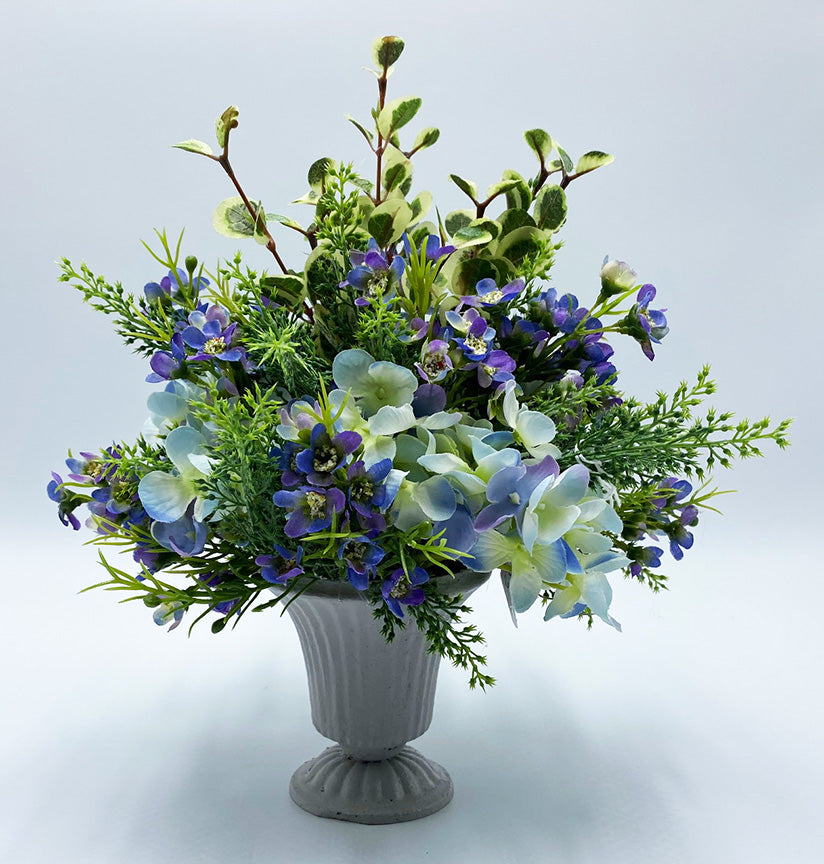 An image of artificial arrangement features violet wax flowers, blue hydrangea and a variety of muted greenery.  The vessel is flat gray and fluted with minimal vintage detailing.