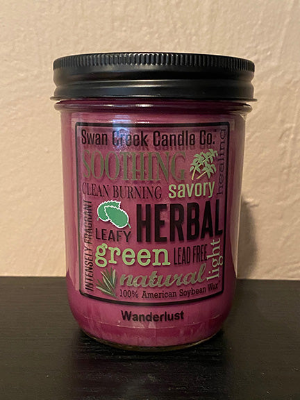 Image of a mason jar candle with burgundy colored wax.  Jar has a black lid and a clear label on the front with several words and phrases in a variety of fonts.  'Swan Creek Candle Co., Soothing, Savory, Green, Lead Free'.  Label is removable.