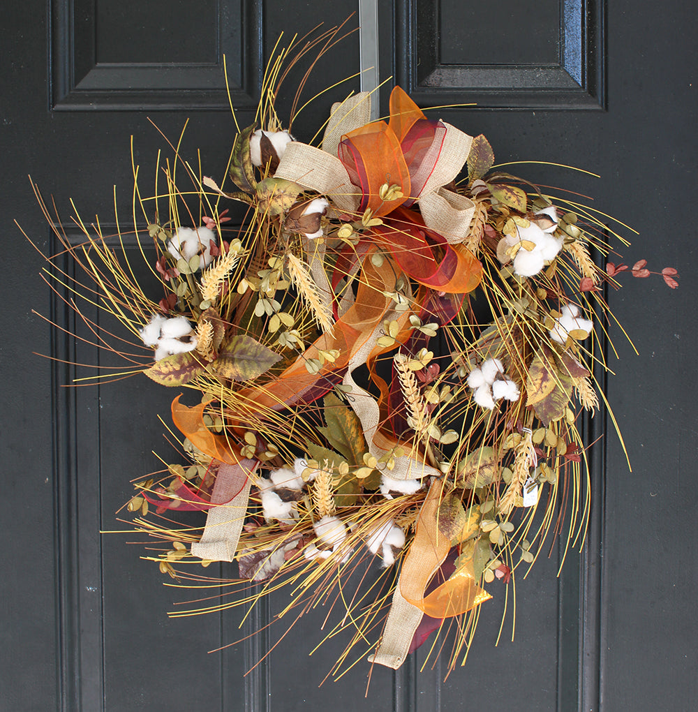 Fall wreath with cotton and wheat on black door