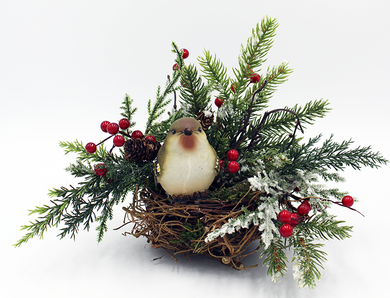 Birds nest floral arrangement with a small brown bird with white chest sitting in a nest surrounded by evergreens, berries, and pinecones.