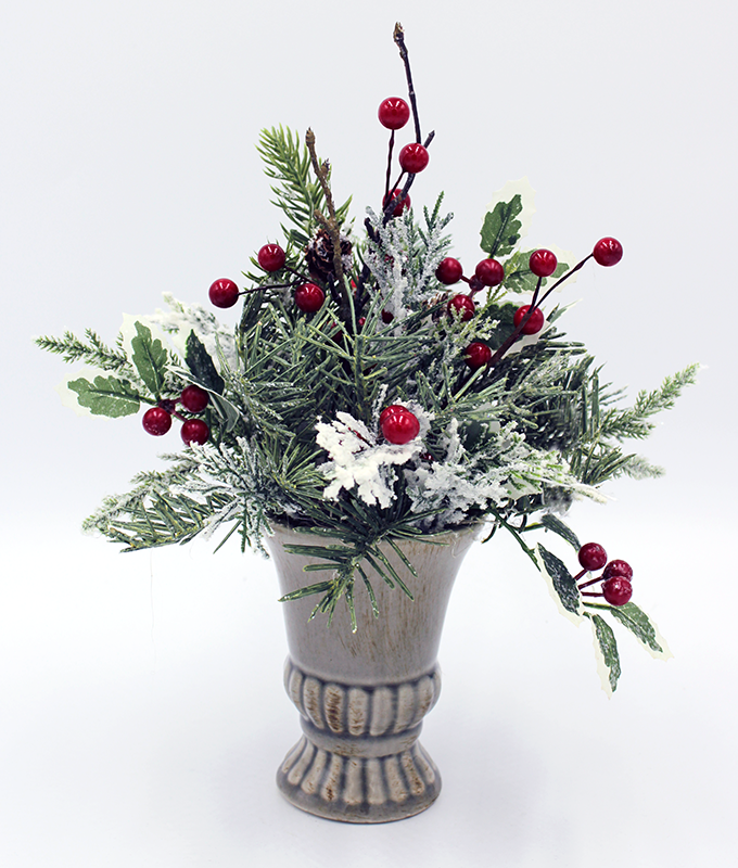 A winter evergreen and berry arrangement in a gray/green vase.  The greens are lightly flocked and twigs with pinecones are interspersed throughout.
