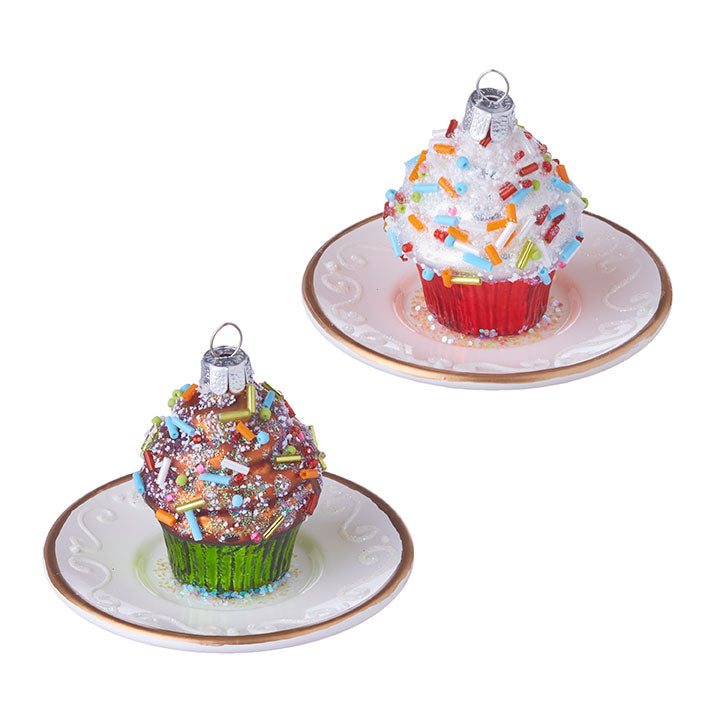 Two cupcake ornaments on a white background.  The ornament on the left is of a chocolate frosted cupcake with green wrapper on a white saucer.  The cupcake on the right is a vanilla frosted cupcake with red wrapper on a white saucer.  Both are decorated with rainbow sprinkles and a dusting of glitter.
