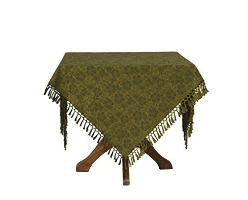 Green jacquard table cloth with fringe on a table.  Pattern is of peonies and accompanying leaves.