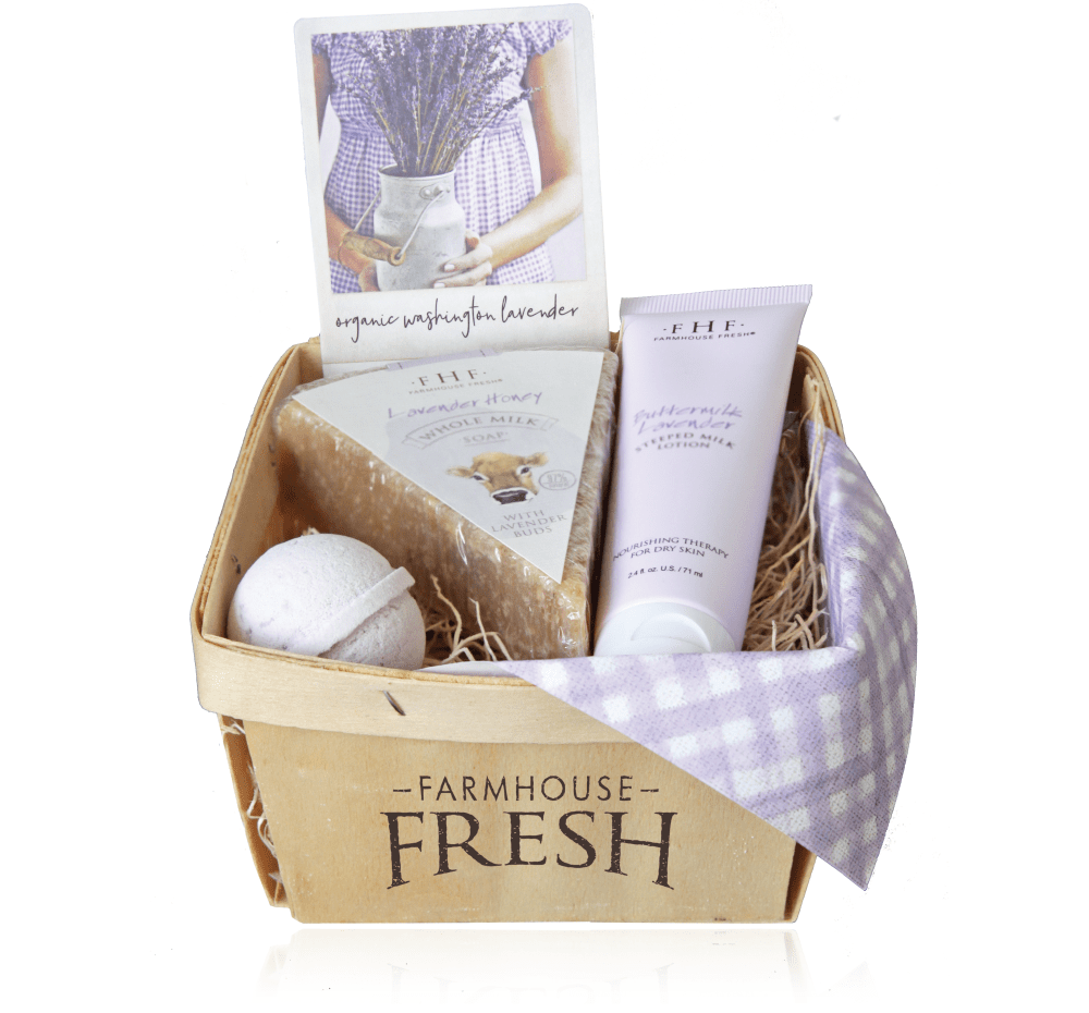 A gift basket with soap, hand lotion and a bath fizzer sitting in a bed of raffia with a purple and white check napkin draped over the front right corner