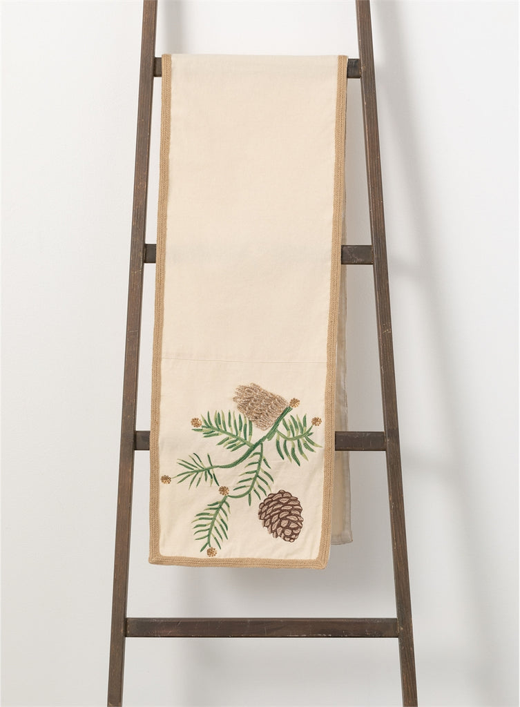 Ivory table runner with jute border folded over the top rung of a ladder leaning against a wall.  The table runner has embroidered evergreen and pinecones and beads and sequins at the end of the evergreens.