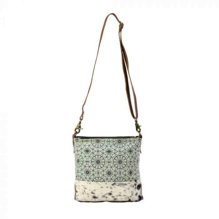 Green and dark gray ogee patterned canvas bag with white and black spotted cow hair trim at the bottom.  A thin dark brown strap is stretched upwards to a hook.