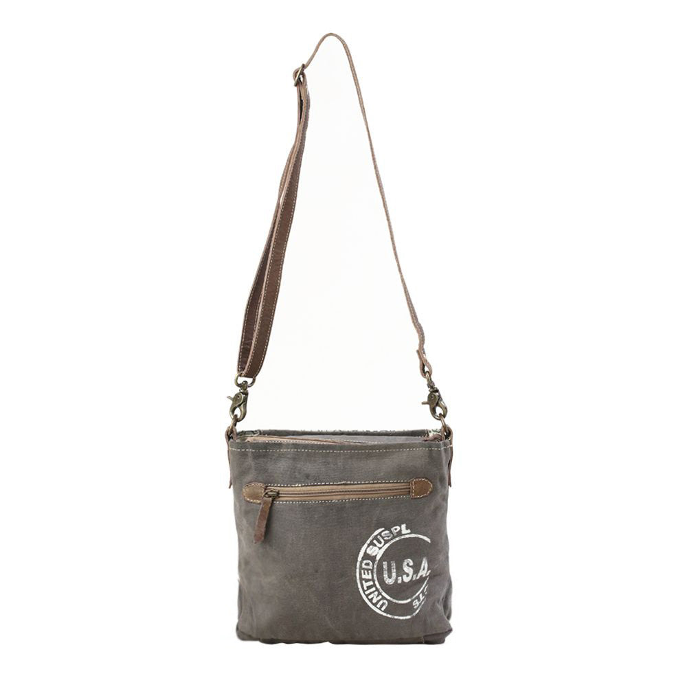 The back of a shoulder bag, the canvas is dark gray and features a large round printed stamp graphic that says 'U.S.A.' in the middle.