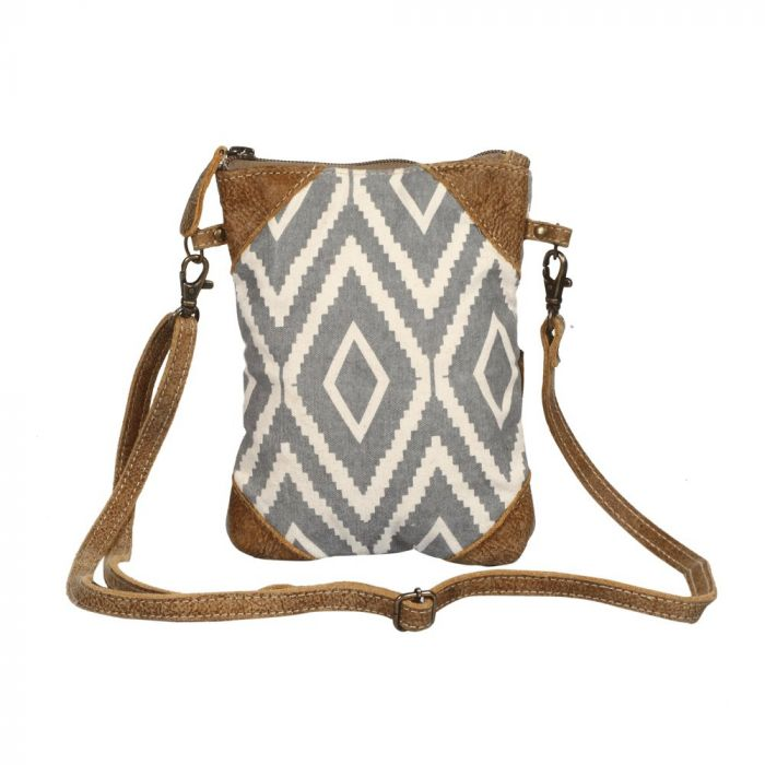 Rectangular cross body bag with a gray and off white diamond pattern, and brown leather triangular details in each of the 4 corners.  The thin brown strap is in front of the bag.