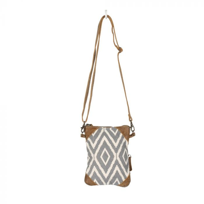 Rectangular cross body bag with a gray and off white diamond pattern, and brown leather triangular details in each of the 4 corners.  The bag is suspended by its thin brown strap from a white hook.