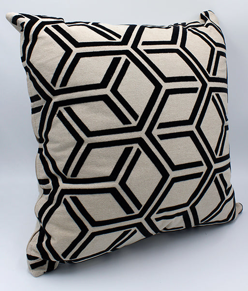 Tan pillow with black interlocking hexagon pattern sitting on a white background.