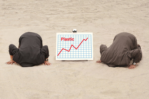 Littorary - Suited men burying heads in sand next to chart showing increasing levels of plastic
