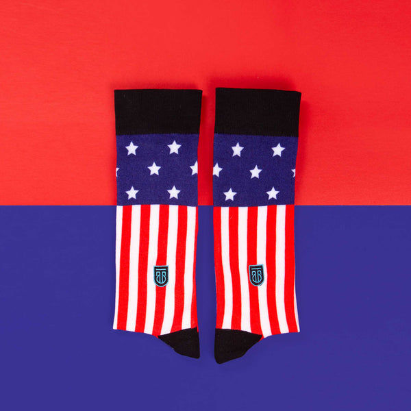 Styled product photo showing pair of folded Tall Order Stars and Stripes socks on a contrasting red and blue background.