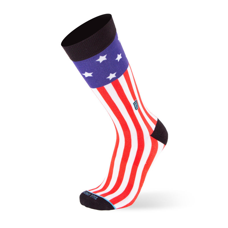 View of outside of sock showing black support band, toe and heel along with red, white, and blue stars and stripes pattern. Tall Order logo is embroidered above the outside of the ankle.
