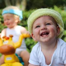Load image into Gallery viewer, Bumpa Banz baby smiling and wearing yellow bumpa banz head protection.