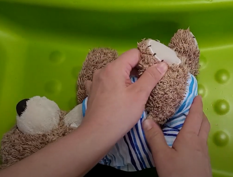 fitting cloth diaper onto baby - tuck edges into leg creases